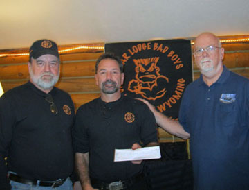 Rick Young (left) and Tom Kostreba (middle) of the Bear Lodge Bad Boys Riding Club present a check for $1,000 to Jack Welch of BRC